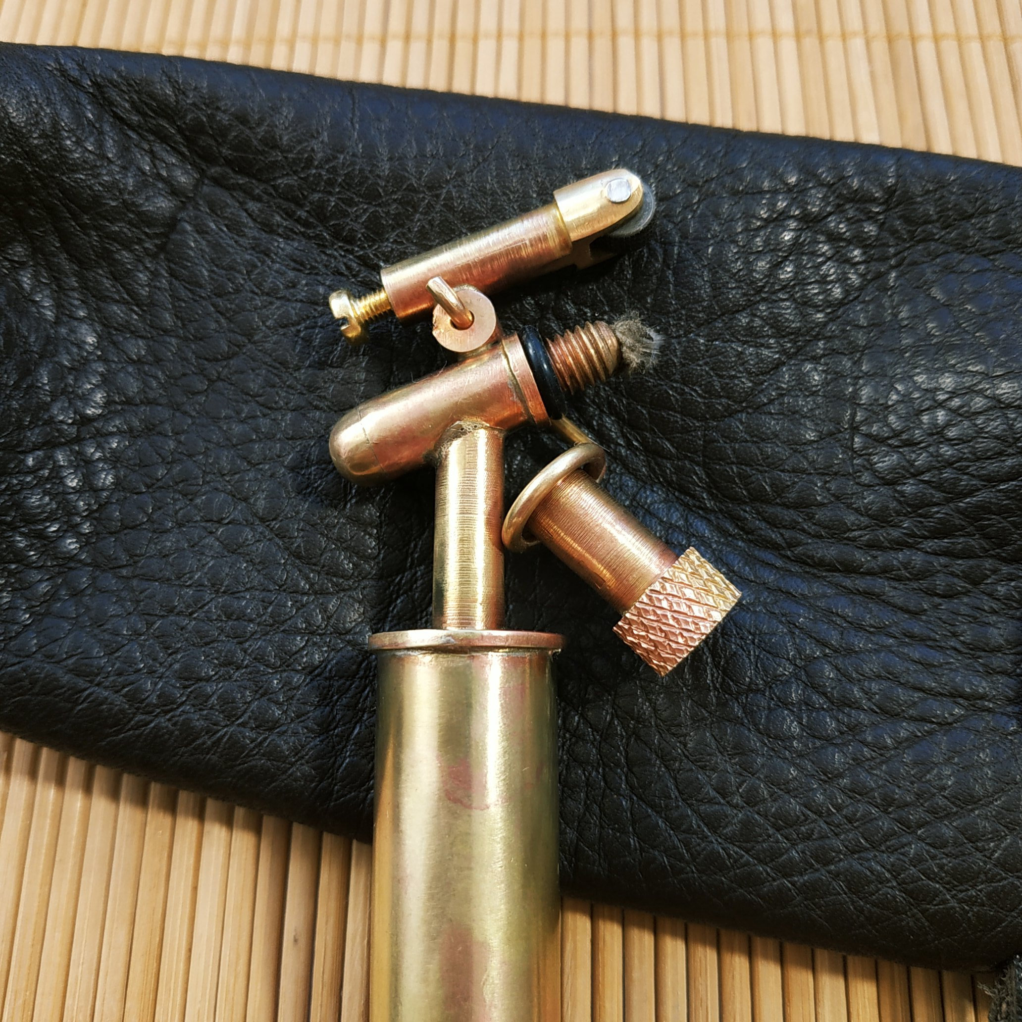 golden lighter with black leather pouch